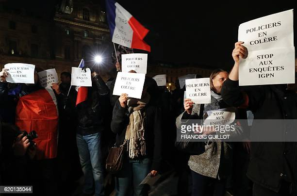 French police officers hold French flags and placards reading 'police officers feel angry ' as they demonstrate next to the Louvre Pyramid in the...