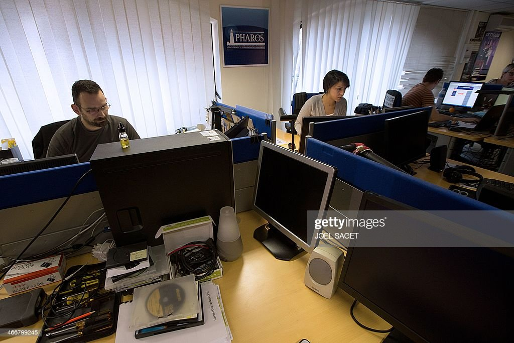 French police officers of the PHAROS internet investigation unit work in Nanterre, near Paris, on February 4, 2014. PHAROS is part of the French Anti-Cybercrime Office (OCLCTIC).