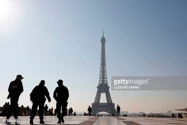 French police officers patroll the Human Rights plaza on the Trocadero facing the Eiffel Tower on April 21 2017 in Paris a day after a gunman opened...