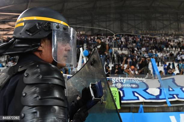 French police officers secure the pitch at the end of the French L1 football match Olympique of Marseille versus Rennes at the Velodrome stadium in...