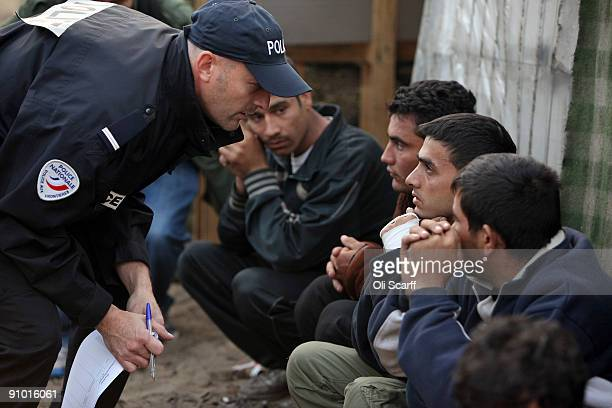 French police officers speak to detained migrants and protesters from the makeshift migrant camp known as 'The Jungle' adjacent to a ferry terminal...