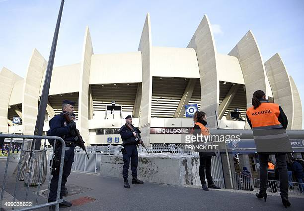 French police officers stand guard as receptionists wait to greet spectators outside the Parc des Princes stadium in Paris before the French L1...