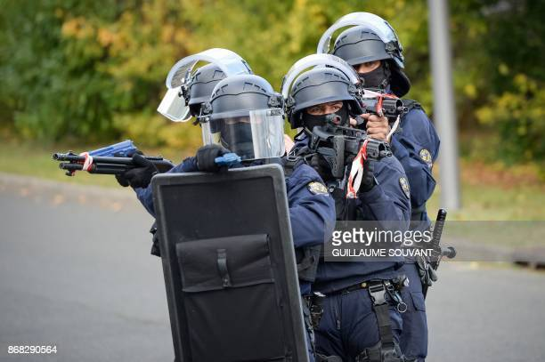 French police officers stand guard as they prepare an evacuation of the hostages during an exercise simulating a terrorist attack inside the theatre...