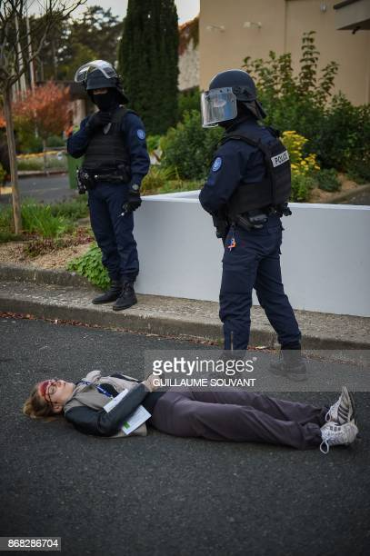French police officers stand guard by a victim lying on the ground as they prepare an evacuation of the hostages during an exercise simulating a...