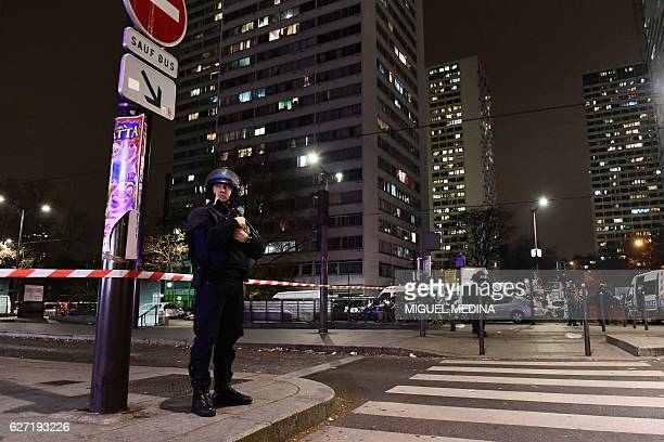 French police officers stand guard inside a security perimeter established as a robber armed with a handgun is holding seven people in a travel...