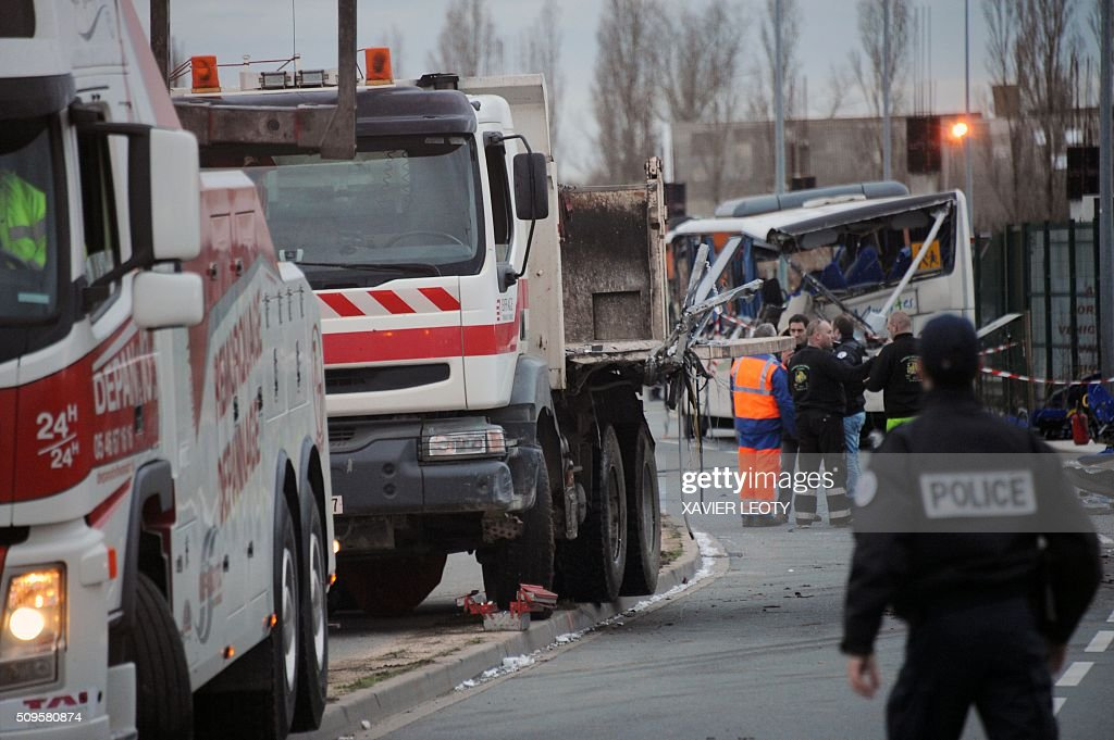 French police officers stand next to the wreckage of a truck after it crashed into school bus in Rochefort on February 11, 2016, killing at least six children, police said, a day after another road accident involving a school bus left two youngsters dead. The head-on smash with a lorry carrying rubble came around 7:15 am (0615 GMT) in Rochefort in the western Charente-Maritime region. The school bus was carrying about 17 people, and three children suffered minor injuries in the accident, a police source said. / AFP / XAVIER LEOTY