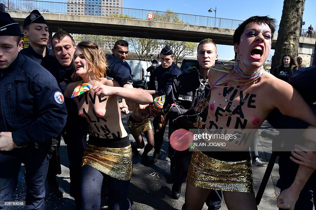 French police officers try to restrain topless Femen activists as they protest outside a banquet by France's far-right Front National (FN) party in honour of Jeanne d'Arc (Joan of Arc) at the Porte de La Villette in Paris on May 1, 2016. / AFP / ALAIN
