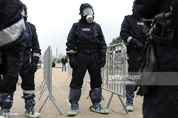 French police officers wear gas masks during a simulation of terrorist attack in football fanzone in Nimes on March 17 2016 as part of Euro 2016 The...