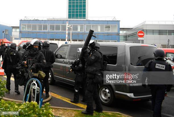 French Police RAID unit officers secure the grounds at Paris' Orly airport on March 18 2017 following the shooting of a man by French security forces...