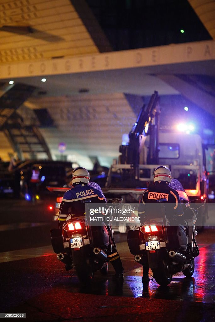 French police stand by as drivers of Uber and other ride-hailing companies, known in France as 'voitures de tourisme avec chauffeur' (VTC), a class of companies that allow passengers to book rides with independent professional chauffeurs, gather at Porte Maillot in Paris on February 11, 2016, to defend jobs they believe are threatened by measures the government recently announced in favor of taxis. / AFP / MATTHIEU ALEXANDRE