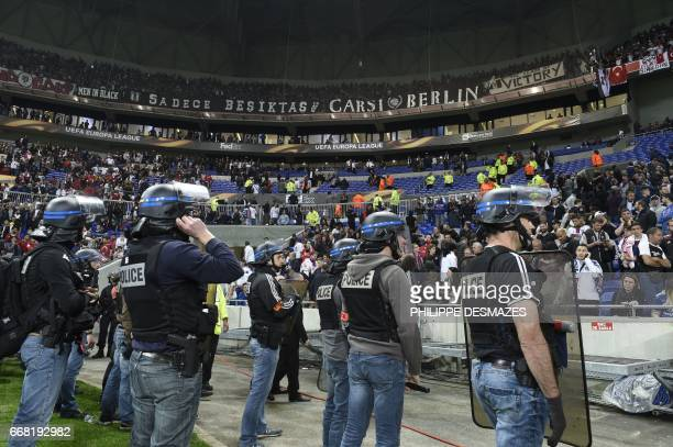 French police stand guard after Besiktas' and Lyon's fans fought before the UEFA Europa League first leg quarter final football match between Lyon...