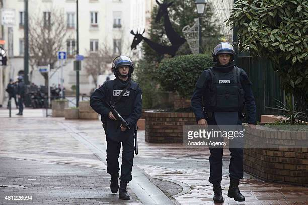 French police stand guard around the kosher supermarket at Port de Vincennes where at least five people have been taken hostage by a gunman suspected...