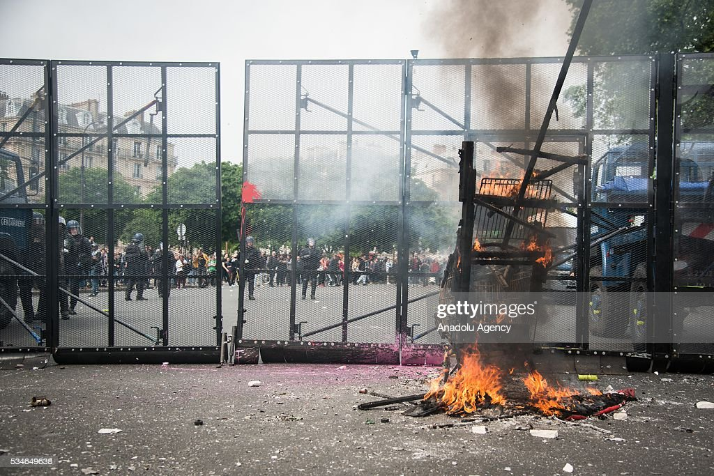French police stand guard behind a fire during the protest against French government's labor law reform in Paris, France on May 26, 2016.