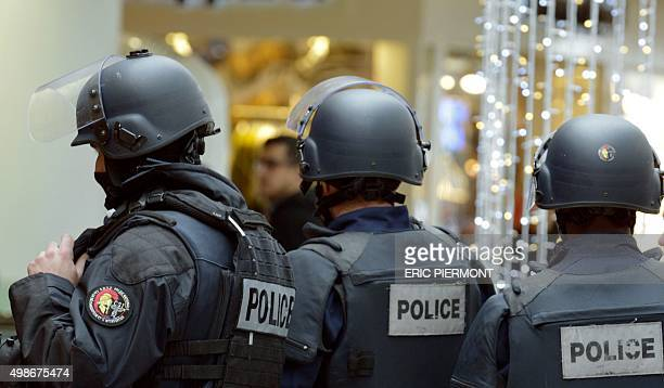 French police stand guard during the visit of the French Economy minister in La Defense business district near Paris on November 25 as part of...