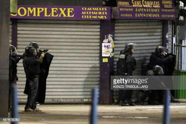 French Police stand in combat position as special forces raid an appartment hunting those behind the attacks that claimed 129 lives in the French...