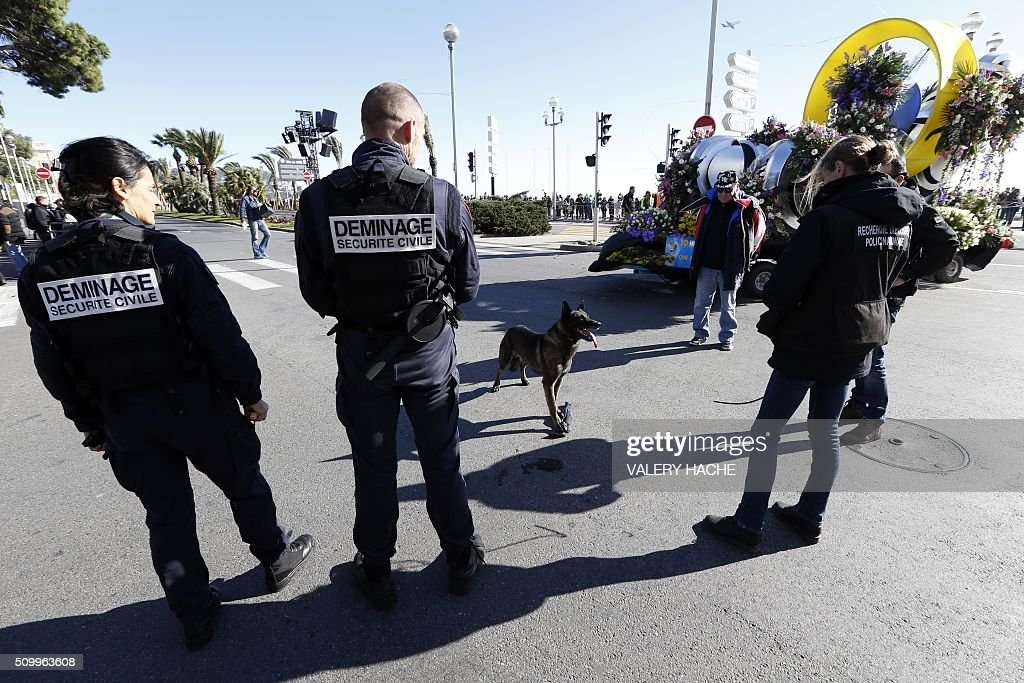 French police stand watch during the 132nd Nice Carnival, on February 13, 2016. The carnival runs from February 13 until 28 February 2016, and this year celebrates 'King of Medias'. / AFP / VALERY HACHE