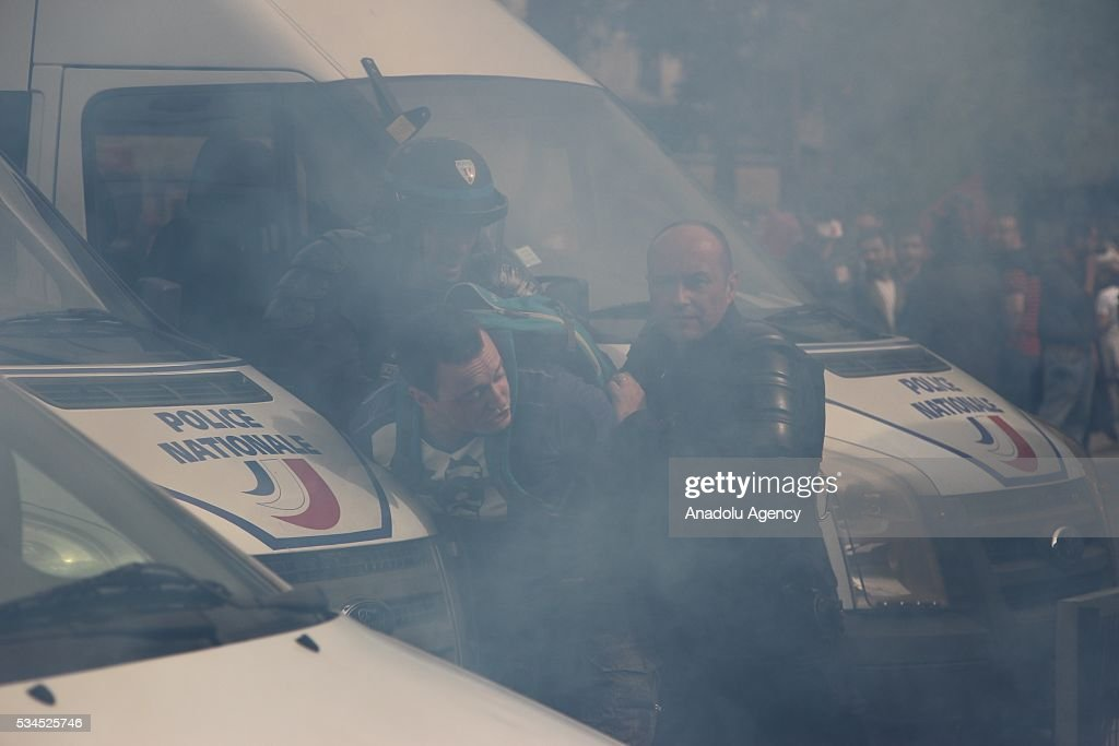 French police take a protester into custody during the protests against French government's labor law reform in Paris, France on May 26, 2016.