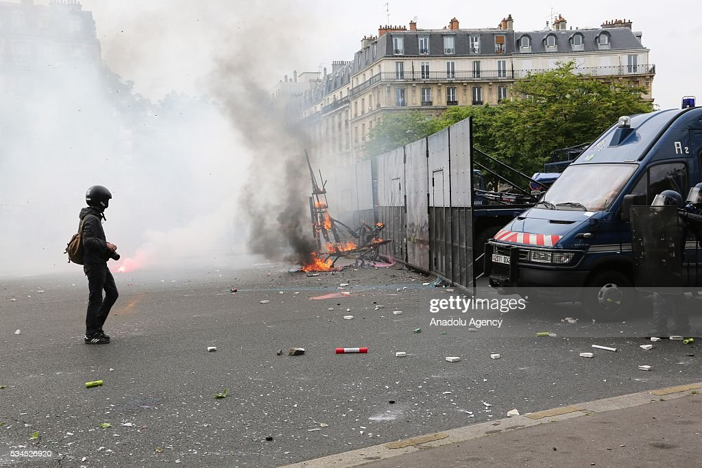 French police use tear gas to disperse protesers during General Confederation of Labour's (CGT) 8th widespread protests all around the France for protesting French government's labor law reform in Paris, France on May 26, 2016.