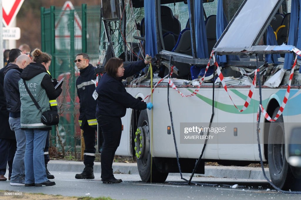 French police work near the wreckage of a school bus after it crashed into a truck in Rochefort on February 11, 2016, killing at least six children, police said, a day after another road accident involving a school bus left two youngsters dead. The head-on smash with a lorry carrying rubble came around 7:15 am (0615 GMT) in Rochefort in the western Charente-Maritime region. / AFP / XAVIER LEOTY