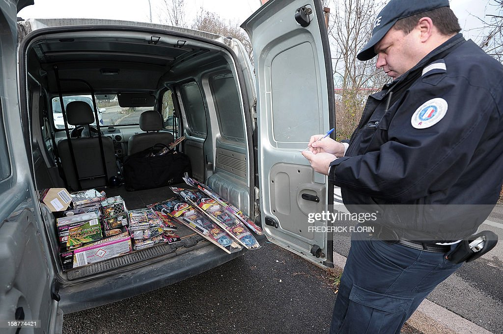 A French policeman confiscates fireworks as police control cars on December 28, 2012 at the border between France and Germany in the eastern French city of Strasbourg. Tighter controls are organised at the border, three days ahead of the New Year's eve, as legislation on firecrackers and fireworks is less restrictive in Germany than in France.