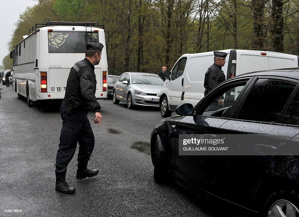 A French policeman controls a car as people arrive to attend the 'Frenchtek 23' Teknival music festival near Salbris, central France on April 30, 2016. / AFP / GUILLAUME