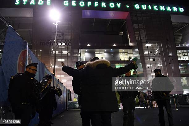 A French policeman frisks a man upon his arrival to attend the French L1 football match between SaintEtienne and Marseille at the Geoffroy Guichard...