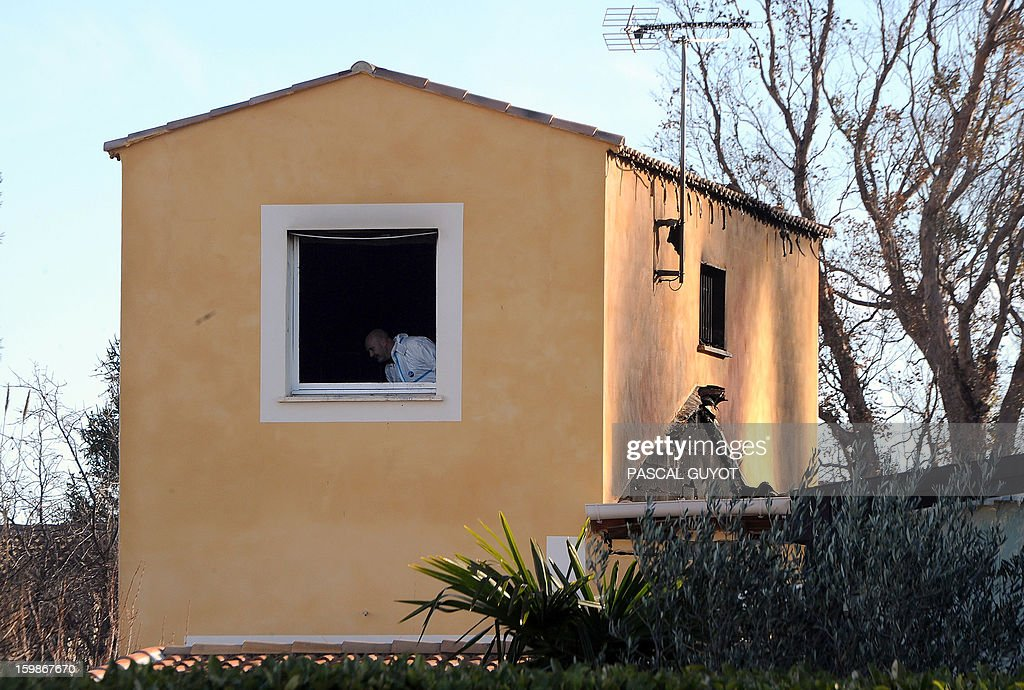 A French policeman is seen throught a window of a house where five people were found dead on January 22, 2013 in Garons, near Nimes, southern France. The bodies of two adults and three children were found by firemen after a neigbour called for a fire in the afternoon. AFP PHOTO / PASCAL GUYOT