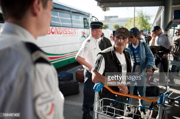 A French policeman looks at people belonging to the Roma community who agreed to a socalled 'voluntary return procedure' who arrive for boarding...