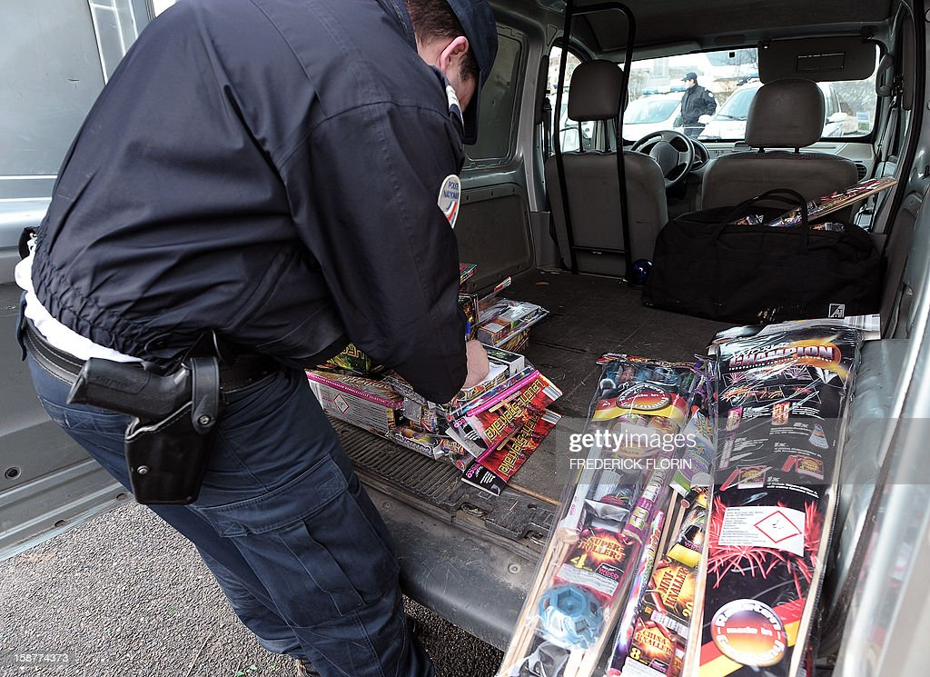 A French policeman looks at seized fireworks on December 28, 2012 at the border between France and Germany in the eastern French city of Strasbourg. Tighter controls are organised at the border, three days ahead of the New Year's eve, as legislation on firecrackers and fireworks is less restrictive in Germany than in France.