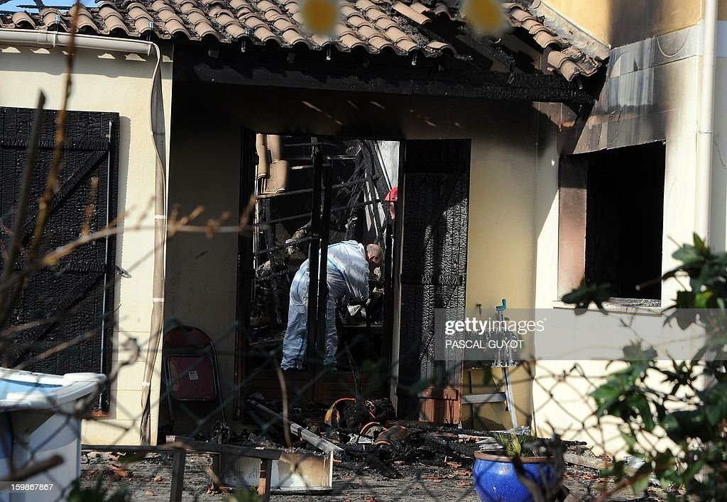 A French policeman search index a house where five people were found dead on January 22, 2013 in Garons, near Nimes, southern France. The bodies of two adults and three children were found by firemen after a neigbour called for a fire in the afternoon. AFP PHOTO / PASCAL GUYOT
