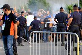 A French policeman sprays tear gas to keep supporters away before the French L1 football match Bastia against Marseille on August 9 2014 at the...