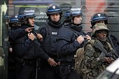 French policemen and soldiers stand guard in the northern Paris suburb of SaintDenis city center on November 18 as French Police special forces raid...