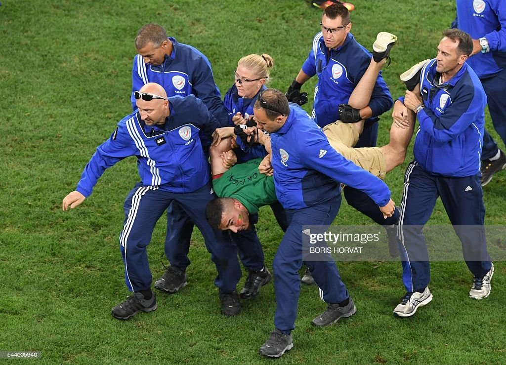 French policemen arrest a Portuguese supporter who invaded the pitch during the Euro 2016 quarter-final football match between Poland and Portugal at the Stade Velodrome in Marseille on June 30, 2016. / AFP / BORIS