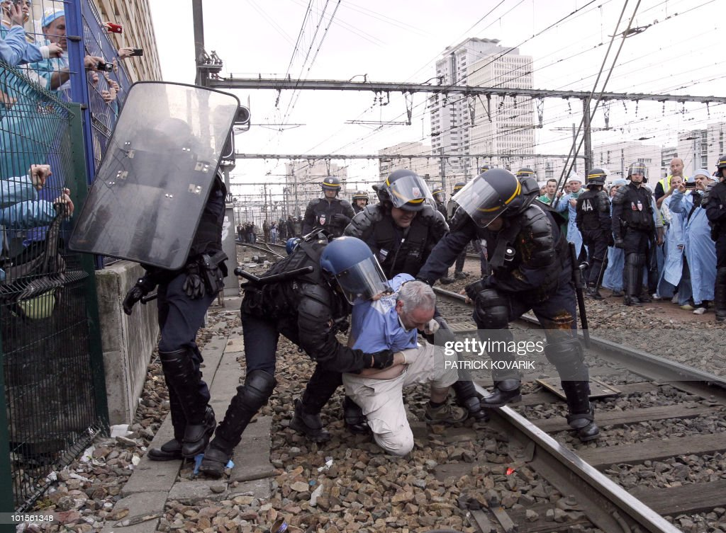 French policemen evacuate a man during a demonstration of French anaesthetist nurses as they stand on tracks near the Montparnasse train station on May 18, 2010 in Paris, blocking the speed train (TGV) traffic, to protest against their work conditions.
