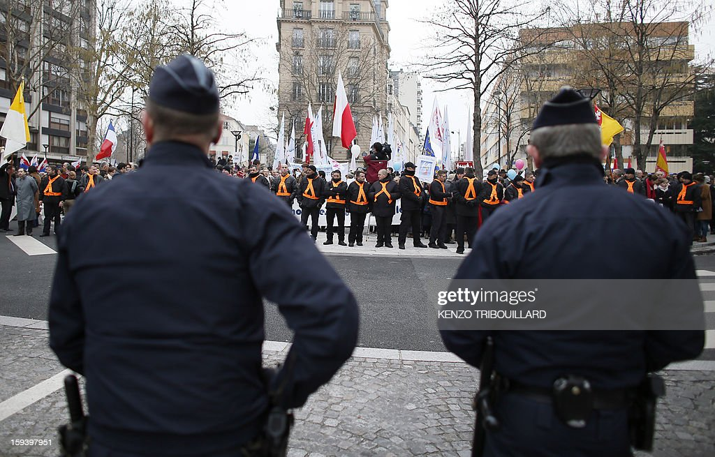 French policemen face demonstrators during a protest organized by fundamentalist Christians group Civitas Institute against same-sex marriage on January 13, 2013 in Paris. Tens of thousands march in Paris on January 13 to denounce government plans to legalise same-sex marriage and adoption which have angered many Catholics and Muslims, France's two main faiths, as well as the right-wing opposition. The French parliament is to debate the bill -- one of the key electoral pledges of Socialist President -- at the end of this month.