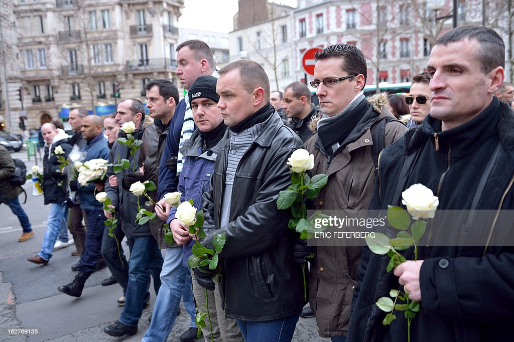 French policemen hold white roses as they take part in a silent march on February 26, 2013 in Paris, in the memory of two of their colleagues, killed in a collision five days before in Paris during a high-speed chase. An alleged drunk driver killed the two Paris police officers after slamming his black Land Rover into their cruiser during a high-speed chase on the ring road around Paris.