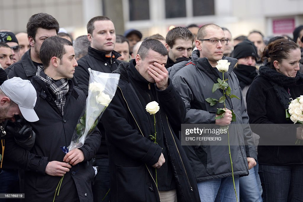 French policemen holding white roses at the end of a silent march pay respect to their two colleagues killed in a collision five days before in Paris during a high-speed chase, on February 26, 2013 in Paris. An alleged drunk driver killed the two Paris police officers after slamming his black Land Rover into their cruiser during a high-speed chase on the ring road around Paris. AFP PHOTO / ERIC FEFERBERG