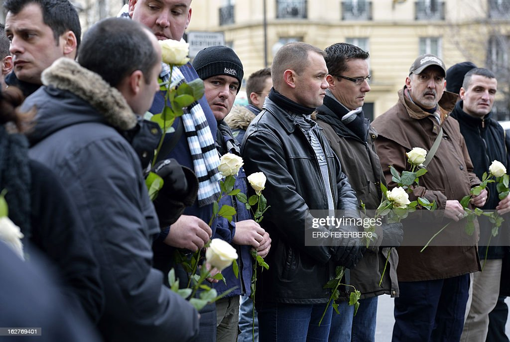 French policemen holding white roses at the end of a silent march pay respect to their two colleagues killed in a collision five days before in Paris during a high-speed chase, on February 26, 2013 in Paris. An alleged drunk driver killed the two Paris police officers after slamming his black Land Rover into their cruiser during a high-speed chase on the ring road around Paris.