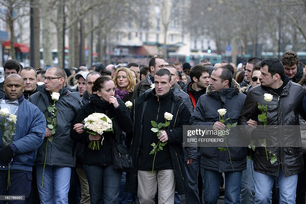 French policemen holding white roses take part in a silent march on February 26, 2013 in Paris, in the memory of two of their colleagues, killed in a collision five days before in Paris during a high-speed chase. An alleged drunk driver killed the two Paris police officers after slamming his black Land Rover into their cruiser during a high-speed chase on the ring road around Paris. AFP PHOTO / ERIC FEFERBERG