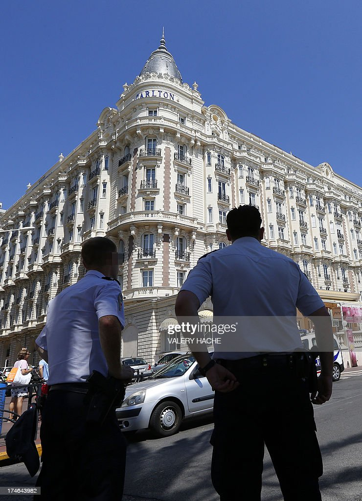 French policemen keep watch outside the Carlton Hotel on July 28, 2013 in the French Riviera resort of Cannes, after an armed man held up the jewellery exhibition 'Extraordinary diamonds' of the Leviev diamond house, making away with jewels estimated to be worth about 40 million euros ($53 million), according to investigators. The lone gunman managed to evade security and escape with a briefcase containing the valuable jewellery. AFP PHOTO / VALERY HACHE