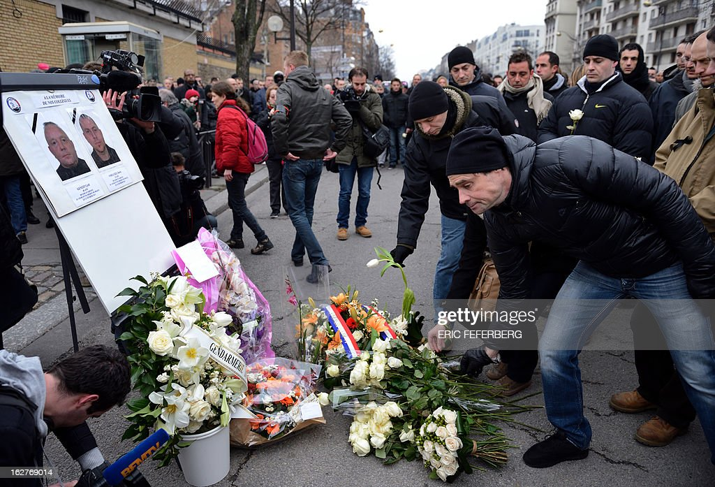 French policemen lay white roses in front of portraits of their two colleagues, killed in a collision five days before in Paris during a high-speed chase, after attending a silent march in their memory on February 26, 2013 in Paris. An alleged drunk driver killed the two Paris police officers after slamming his black Land Rover into their cruiser during a high-speed chase on the ring road around Paris.