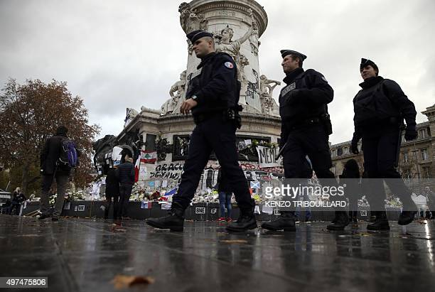 French policemen patrol next to the makeshift memorial made up with flowers candles and messages on November 17 at the Place de la Republique square...