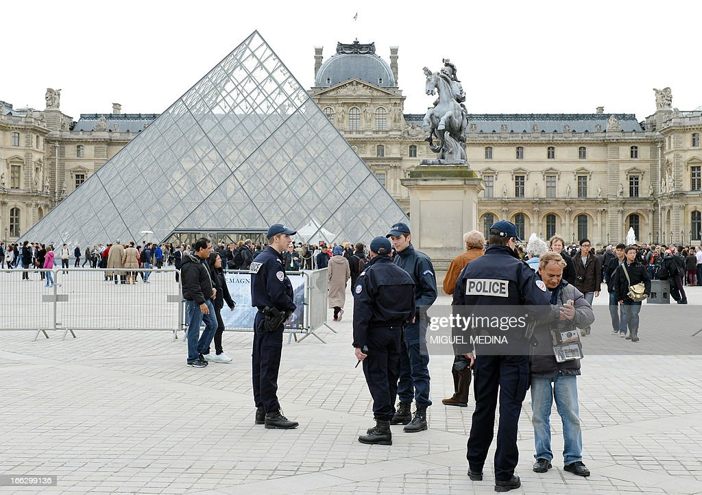French policemen patrol on April 11, 2013 at the 'Cour Carree' of the Louvre Museum in Paris. Paris's Louvre museum today reopened its doors to the public after a walkout by some staff in protest at gangs of pickpockets operating at the world famous art gallery. Around 20 police officers have now been drafted in to patrol the museum in response to staff concerns, Louvre officials told AFP. The day before, the Louvre failed to open when around 200 employees refused to work saying the museum had become plagued by gangs of increasingly aggressive pickpockets, many of whom were children.