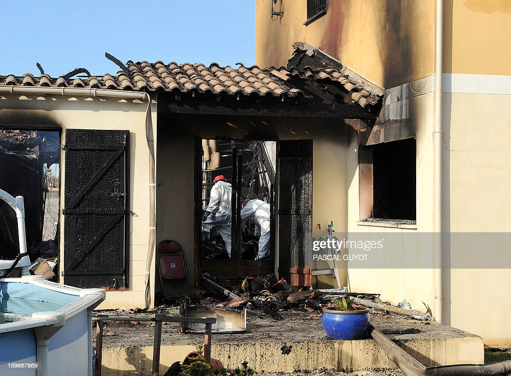 French policemen search index a house where five people were found dead on January 22, 2013 in Garons, near Nimes, southern France. The bodies of two adults and three children were found by firemen after a neigbour called for a fire in the afternoon.
