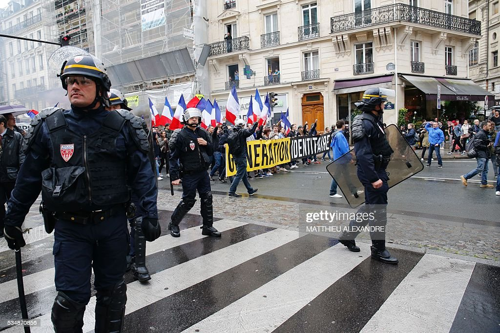 French policemen stand guard as protesters from far-right movement Generation Identitaire take part in a demonstration against migrants on May 28, 2016 in Paris. / AFP / MATTHIEU