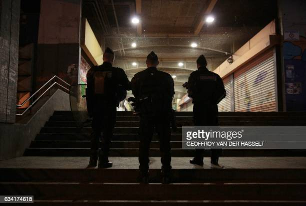 TOPSHOT French policemen stand guard at the Rose des Vents district also known as the Cite des 3000 in AulnaysousBois northeast of Paris on February...