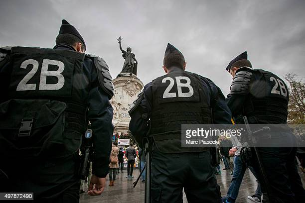 French policemen stand guard in front of a makeshift memorial for the victims of the attacks on Place de la Republique on November 19 2015 in Paris...
