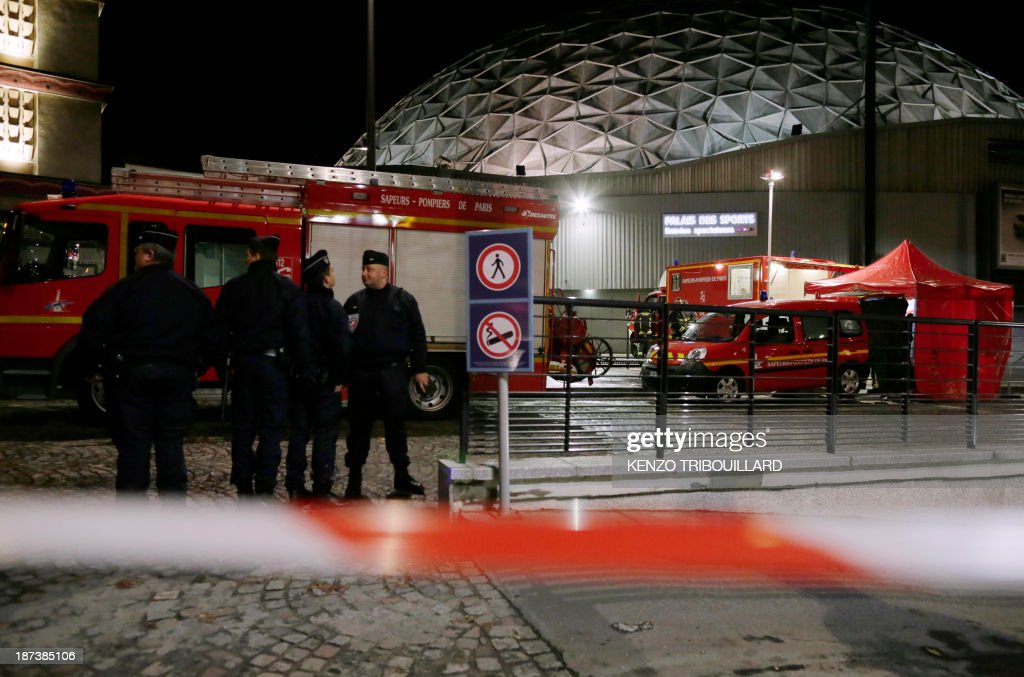 French policemen stand guard outside the Palace of Sports at the Porte de Versailles in Paris following a blast on November 8, 2013. At least seven people were injured when an accidental explosion took place during a rehearsal of the musical '1789, The Lovers of Bastille'.