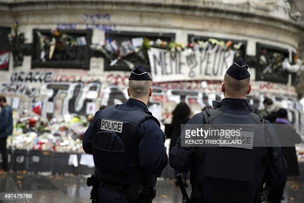 French policemen stand in front of a makeshift memorial made up with flowers candles and messages on November 17 at the Place de la Republique square...