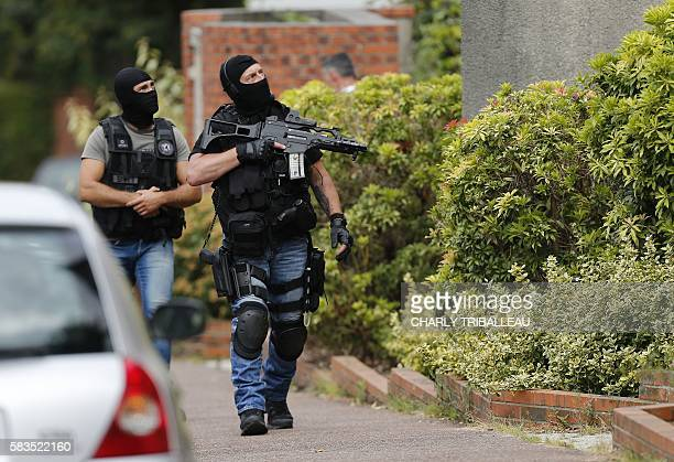 French policemen stand in the street during a search in a house on July 26 2016 in the Normandy city of SaintEtienneduRouvray after a priest was...